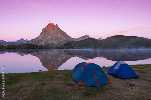 Foto auf Leinwand Flieder Tents next to the lake of Gentau, Ayous, and the Pico de Midi d'Ossau is reflected in its waters, Pyrenees, France.
