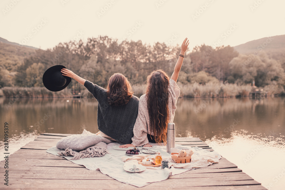 Fototapeta Two women friends having picnic in autumn forest near lake.