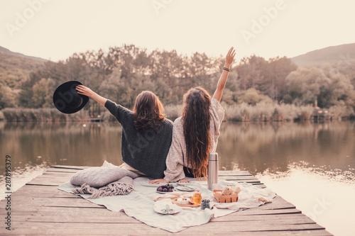 Two women friends having picnic in autumn forest near lake.