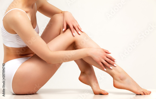 Wellness and beauty concept, beautiful slim woman in white underwear sitting on white floor - fototapety na wymiar