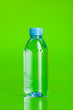 canvas print picture - Crystal clear water in a bottle on green background