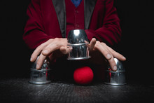 Magician Shows Shell Game Of Thimbles With Circles And Ball, Black Background. Concept Deception, Sleight Hand