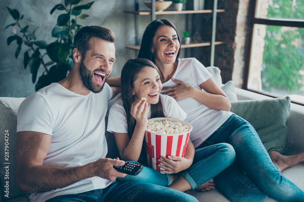 Fototapety, obrazy: Portrait of nice attractive lovely positive glad cheerful cheery family wearing casual white t-shirts jeans denim sitting on sofa having fun watching funny video enjoying spending free time