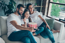 Portrait Of Nice Attractive Lovely Charming Cheerful Cheery Family Wearing Casual White T-shirts Jeans Denim Sitting On Divan Having Fun Watching Series Serial Video Switching Channel Indoors