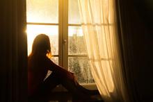 Girl Sitting On A Windowsill A...