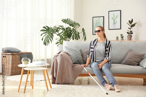 Young blind woman sitting on sofa at home Fototapet