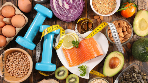 selection of diet food, salmon with dumbbell and healthy food