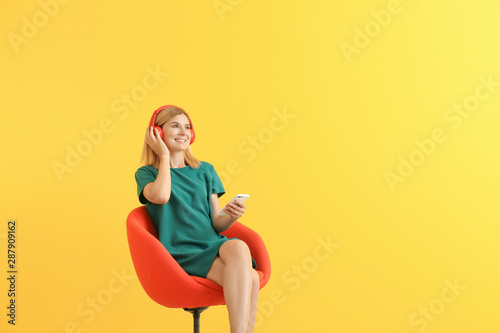 Fotomural  Happy beautiful woman listening to music on color background