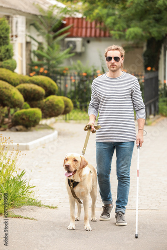Blind young man with guide dog outdoors Wallpaper Mural