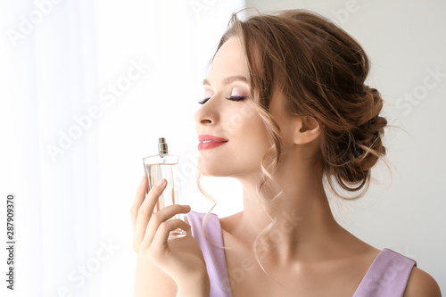 Beautiful young woman with bottle of perfume indoors Fototapet