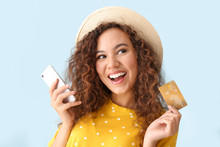 Happy African-American Woman With Credit Card And Mobile Phone On Light Color Background