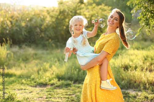 Fototapeta Happy mother and her little daughter blowing soap bubbles outdoors obraz