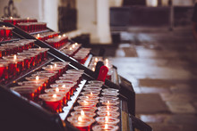 Candles In The Church. Votive Prayer Candles Inside A Catholic Church On A Candle Rack