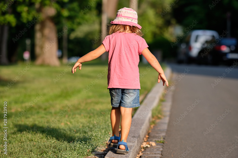 Fototapeta Rear view of a girl child in summer clothing balancing alone on a curb between a lawn and a street in the evening light of a summer day