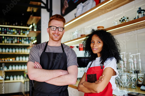 Portrait of professional caucasian barista with crossed hands together with experienced african american waitress in arons smiling at camera Canvas Print
