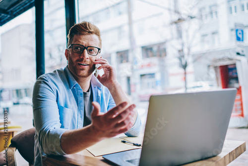 Obraz Caucasian young man in casual wear looking away while discussing new tariff plan with operator during phone call on smartphone device sitting at modern laptop computer using wireless internet - fototapety do salonu