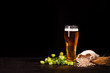 Leinwandbild Motiv Glass of beer with wheat and hop cones on dark wooden background. October fest background