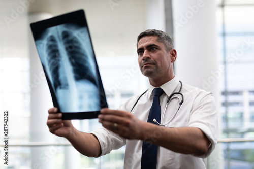 Caucasian male doctor looking at x-ray in clinic