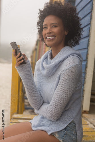 Young African American woman using mobile phone sitting at beach hut