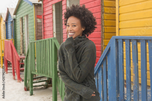 Young African American woman standing at beach hut