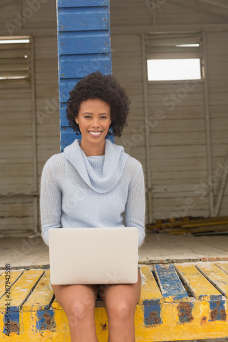 Young African American woman using her laptop at beach hut