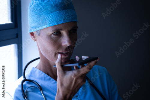 Female surgeon talking on mobile phone at hospital