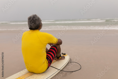 Senior male surfer sitting on the surfboard on beach