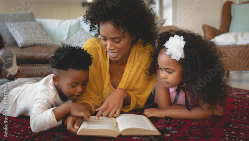 African American mother with her cute children lying on floor and reading a book