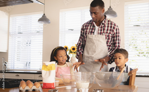 African American father and children baking cookies in kitchen