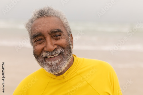 Happy senior man looking at camera on the beach