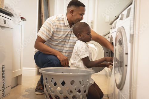 African American father and son washing clothes in washing machine