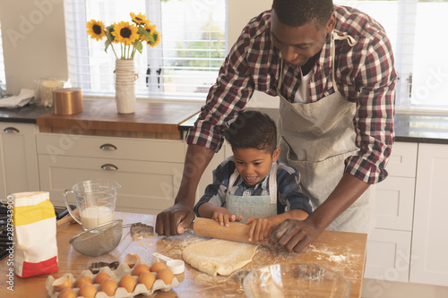 African American father and son rolling out cookie dough in kitchen