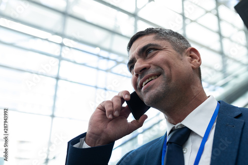 Close-up of Caucasian businessman talking on mobile phone in escalator