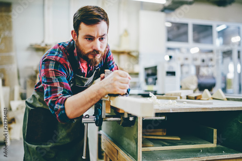 Stampa su Tela Handsome caucasian male joiner standing near table with sawdust working via tool with wood, strong serious foreman repair furniture in his workshop owning restoration and manufacturing business