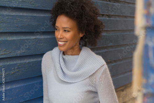 Young African American woman leaning against beach hut