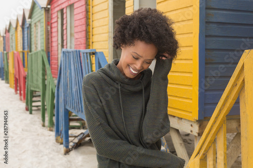 Young African American woman with hand in hair standing at beach hut