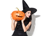Young Brunette Woman In Black Hat And Costume On White Background. Attractive Caucasian Female Model. Halloween, Black Friday, Cyber Monday, Sales, Autumn Concept. Holding Pumpkin. Look Mystic.