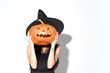 canvas print picture Young brunette woman in black hat and costume on white background. Attractive caucasian female model. Halloween, black friday, cyber monday, sales, autumn concept. Holding pumpkin. Look mystic.