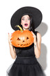 canvas print picture Young brunette woman in black hat and costume on white background. Attractive caucasian female model. Halloween, black friday, cyber monday, sales, autumn concept. Holding pumpkin. Looks shocked.