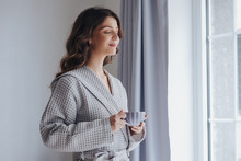 Portrait Of Pretty Woman In Bathrobe Enjoying Morning Standing By The Window And Holding Cup Of Tea.