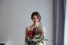 Portrait Of Beautiful Tender Young Smiling Woman Holding Bouquet.