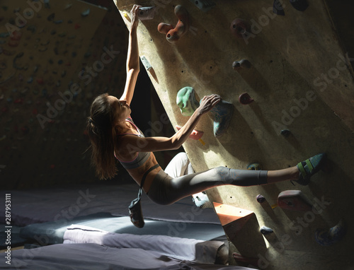 Young Woman Rock climber is Climbing At Inside climbing Gym Canvas Print