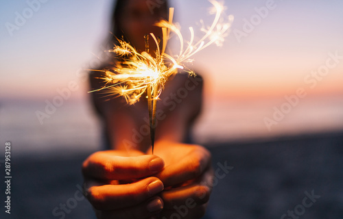 Fényképezés  Young happy woman stands on beach with sparkler in sunset light