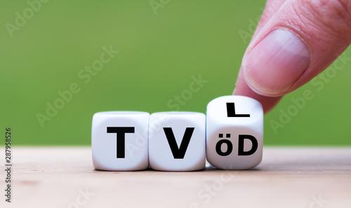 Fotografija  Hand dreht einen Würfel und ändert die Abkürzung TV-L (Tarifvertrag für den öffentlichen Dienst der Länder) in TVöD (Tarifvertrag für den Öffentlichen Dienst), oder umgekehrt