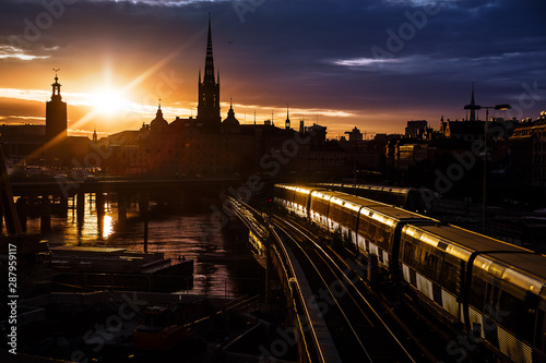 Foto auf Gartenposter Stockholm Stockholm city skyline. The view of Old Town, Gamla Stan, and Riddarholmen Church from The Central Bridge Centralbron with local trains on it during sunset. Sweden.