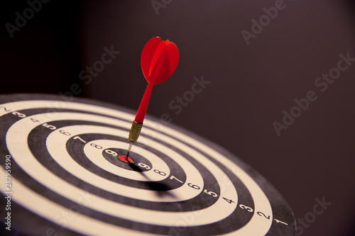 Fotomural  Red dart arrow hitting in the target center of dartboard on bullseye for Business focus concept