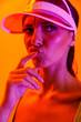 canvas print picture Image closeup of fashionable brunette woman wearing sun visor cap and sportswear posing at camera isolated over orange neon wall