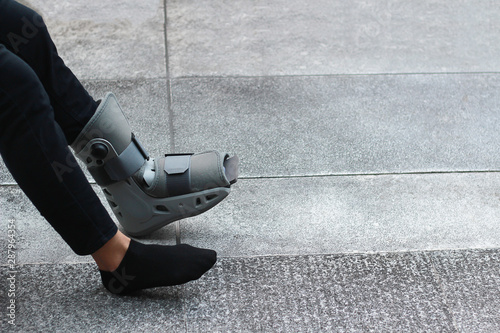 Photo A Asian girl is wearing a ankle support boot after surgery.