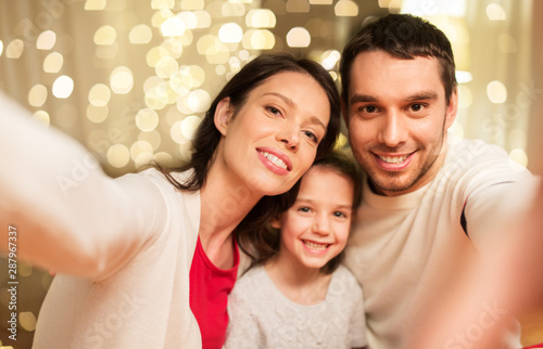Obraz na plátně  family, christmas and holidays concept - happy mother, father and little daughte