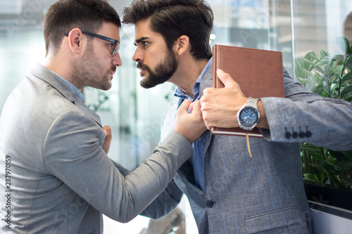 Business conflict between two business men in formal-wear in office Wallpaper Mural